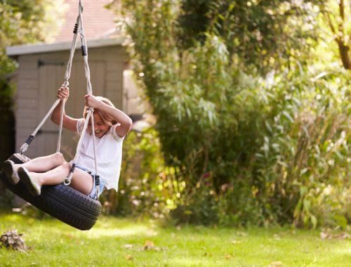 young-girl-playing-on-tire-swing-in-garden-PJQ4ZSN.jpg